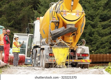 Falcade, Belluno, Italy - August 21, 2015: Cement mixer truck works at building site under construction the new modern cabin lift in the  ski area San Pellegrino