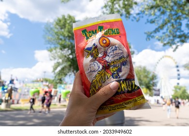 Falcon Heights, Minnesota - August 30, 2021: Hand holds up a Tom Thumb bag of mini donuts at the Minnesota State Fair