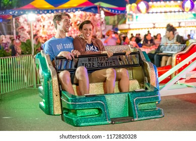 Falcon Heights, MN/USA August 30, 2018 Minnesota State Fair documentary editorial. Brightly lit carnival ride in motion with happy riders.