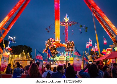 Falcon Heights, MN/USA August 30, 2018 Minnesota State Fair documentary editorial. Brightly lit carnival swing, ride in motion with happy people. Amusement ride, circus, festival.