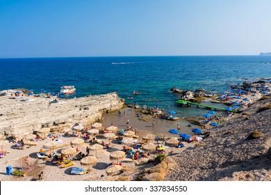 FALIRAKI, RHODES, GREECE â?? AUGUST 2ND 2015 People enjoying sunny weather on a busy Oasis Beach near Faliraki