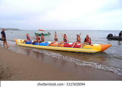 Faliraki, Rhodes, Greece - May 18, 2018: Young guys and girls riding on an inflatable banana, Faliraki, Rhodes Island, Greece