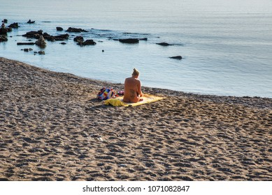 Faliraki,Rhodes,Grece-October.28.2016:Lonely naked girl on a nudist beach, Mandomata in Faliraki, enjoying the morning sun