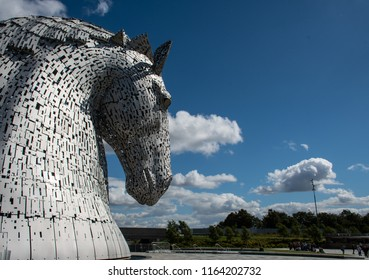 Falkirk, United Kingdom - August 09 2018:   Tourists around the Kelpies - a pair of large horse head statues made from Stainless steel by Sculptor Andy Scott and unveiled in 2013