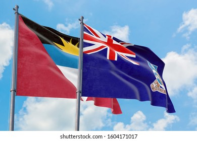 Falkland Islands and Antigua and Barbuda flags waving in the wind against white cloudy blue sky together. Diplomacy concept, international relations.