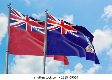 Falkland Islands and Bermuda flags waving in the wind against white cloudy blue sky together. Diplomacy concept, international relations.