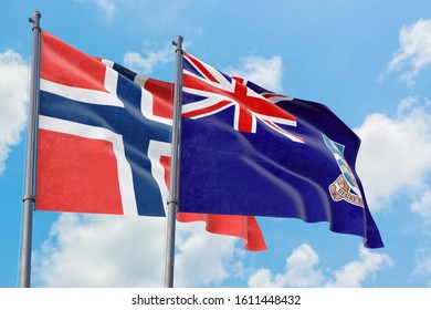 Falkland Islands and Bouvet Islands flags waving in the wind against white cloudy blue sky together. Diplomacy concept, international relations.