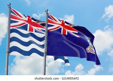 Falkland Islands and British Indian Ocean Territory flags waving in the wind against white cloudy blue sky together. Diplomacy concept, international relations.