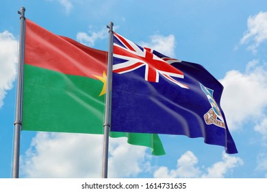 Falkland Islands and Burkina Faso flags waving in the wind against white cloudy blue sky together. Diplomacy concept, international relations.
