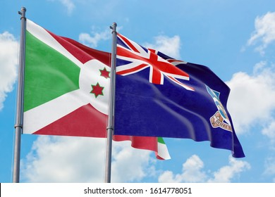 Falkland Islands and Burundi flags waving in the wind against white cloudy blue sky together. Diplomacy concept, international relations.