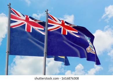 Falkland Islands and Cayman Islands flags waving in the wind against white cloudy blue sky together. Diplomacy concept, international relations.