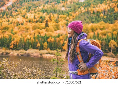 Fall autumn hiker girl outdoor at nature forest lake with backpack for camping travel trip. Happy Asian woman hiking outdoors with bag and hat, cold outerwear gear.