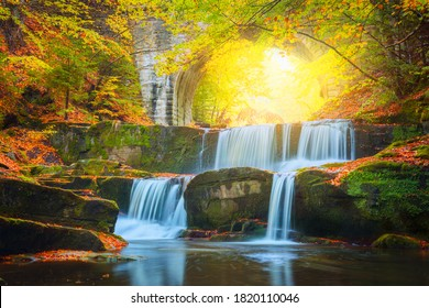 Fall Autumn landscape - river waterfall in colorful autumn forest park with yellow red leaves with old bridge