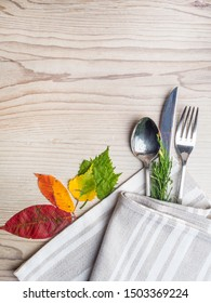Fall or autumn themed place setting with a knife, spoon and fork, napkin on a plate on an arrangement of colorful leaves, copy space