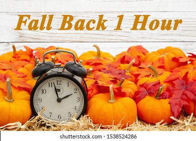 Fall Back 1 hour time change message with a retro alarm clock with orange pumpkins with fall leaves on straw hay with weathered whitewash wood