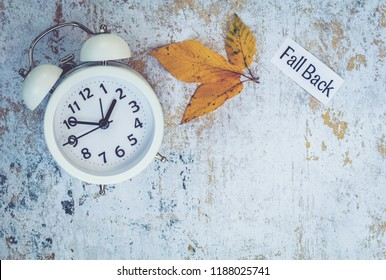 Fall Back Daylight Saving Time concept with fall decor and white alarm clock, flat lay