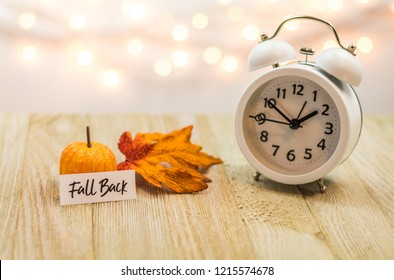 Fall Back Daylight Saving Time concept with white clock and autumn leaves, soft bokeh background on wooden board