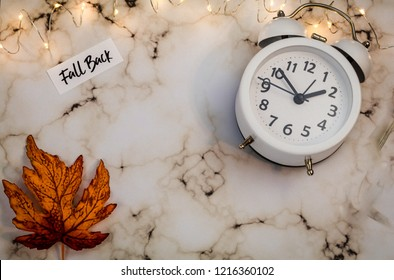 Fall Back Daylight Saving Time concept with white clock and autumn leaves, flat lay on marble
