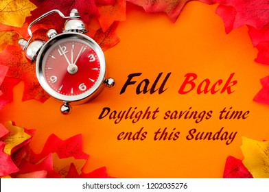 Fall back, the end of daylight savings time and turn clocks back on hour concept with a clock surrounded by dried yellow leaves with the text Fall back, daylight savings time ends this Sunday - Shutterstock ID 1202035276