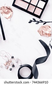 Fall beauty makeup products with rose gold leaves and black ribbon flatlay on white marble