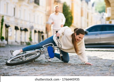 Fall with bike. Young unhappy woman on a city street falling with a bicycle on the road and a man running hurrying behind