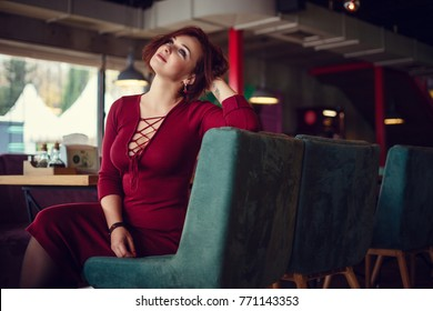 Fall casual fashion, elegant everyday look. Plus size model. Beautiful young woman in a chic red dress with a deep neckline drinking tea in a restaurant