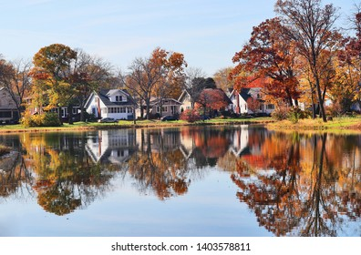 Fall cityscape with private houses neighborhood along a pond. Colorful trees and houses reflected in a water. Midwest USA, Wisconsin. Classic american middle class homes background.