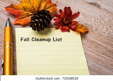 Fall Cleaning List concept on notebook and wooden board