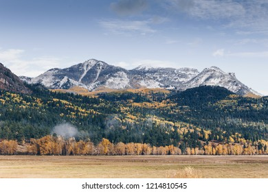 Fall colors over field and first snow in southwestern Colorado mountains, wolf creek pass