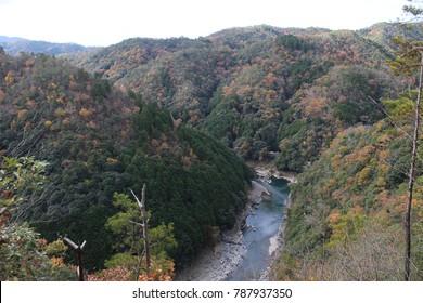 Fall colors over Katsura river at the mountains of Arashiyama, Kyoto, Japan