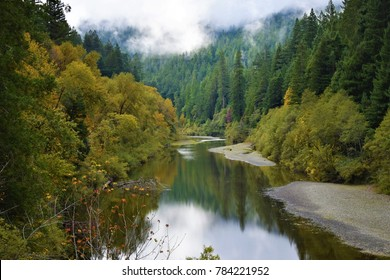 Fall colors reflect off a calm and cool South Fork Eel River within the evergreen redwood forest of Humboldt Redwoods State Park along Avenue of the Giants just north of Weott, California.