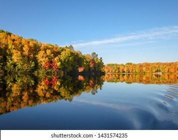 Fall colors trees reflection blue lake waters. Horizontal autumn landscape. No people.