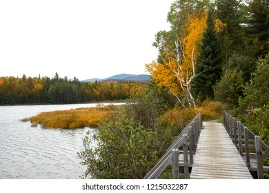 Fall colors and wooden hiking bridge on the shoreline of Stratton Brook Pond in the great north woods of Carrabassett Valley, Maine.
