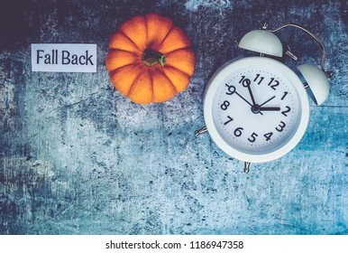 Fall Daylight Saving Time concept with white clock and flowers, flat lay