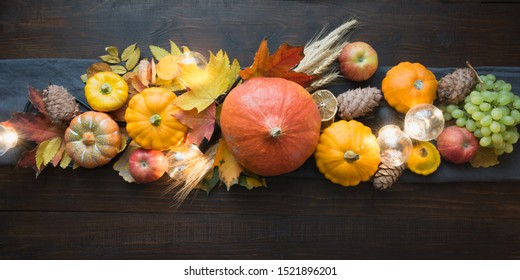 Fall decor for Thanksgiving Day with pumpkins, leaves, apples, lights on wooden table. View from above. Horizontal orientation. Centerpieces Thanksgiving.