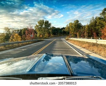 Fall drive view from a vintage classic muscle car, a 1968 Camaro, with the refection of the colorful changing autumn leaves and the cloudy sky reflecting off the hood, and with winding road ahead.