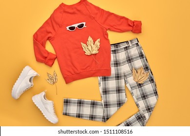 Fall fashion Flat lay. Trendy orange jumper, Stylish trousers, hipster sneakers, autumn Maple Leaf. Creative Woman Clothes Accessories layout. Fall Girl fashionable Outfit, autumnal orange color.
