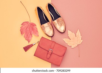 Fall Fashion Glamour Lady Look. Autumn Minimal Design. Flat lay.Trendy Handbag Clutch. Stylish Gold Shoes. Yellow leaves.