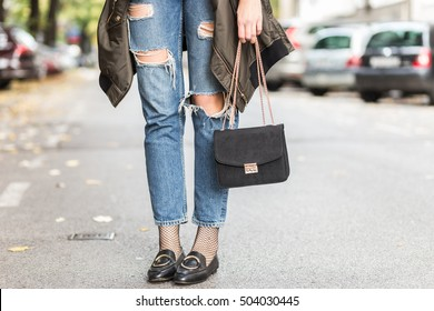 fall fashion outfit details. fashionable woman wearing ripped jeans with loafers, oversized bomber jacket and a trendy black bag.