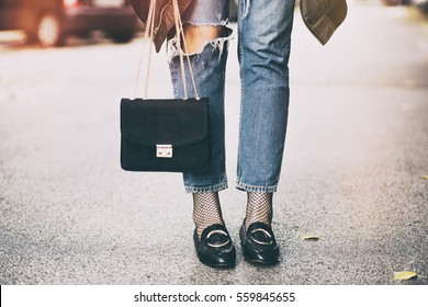 fall fashion outfit details. fashionable woman wearing ripped jeans with loafers, fishnet stockings, oversized bomber jacket and a trendy black bag.
