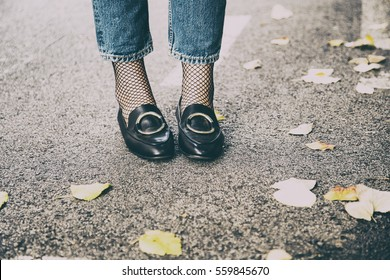 fall fashion outfit details. fashionable woman wearing ripped jeans with loafers and fishnet stockings.