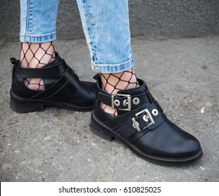 fall fashion outfit details. fashionable woman wearing ripped jeans with loafers, fishnet stockings.