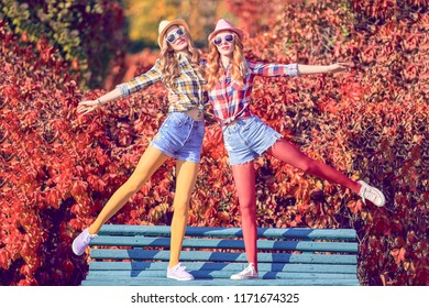 Fall Fashion. Two Young Woman Fooling Around standing on bench in Colorful Park. Lovable Happy Girl Friends Enjoy Nature. Urban Outdoor. Crazy Positive Model in Stylish Trendy Autumn Outfit