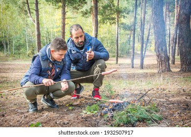 In the fall, father and son sit in the forest near the fire and fry sausages on a stick.