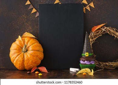Fall festive chalkboard background with pumpkin, leaves, and Halloween treats: candies and witch hat cupcake. Halloween sale mockup with copyspace.