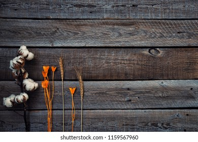 Fall flowers on old grunge wooden barn boards. Autumn composition. Autumn flowers, cotton flower and ears of wheat. Flat lay, top view, copy space. Vintage color. Toned image.