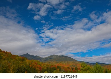 Fall foliage around Mt. Washington and the Presidential Range in New Hampshire, New England on a beautiful autumn day with bright blue skies and fluffy white clouds