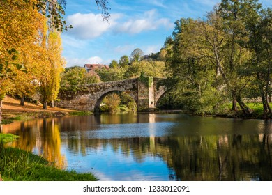 Fall foliage and medieval Roman bridge reflected on the water in the Galician village of Allariz, Ourense.