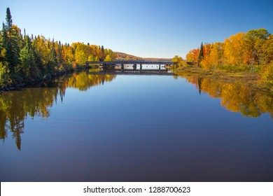 Fall Foliage Panorama. Vibrant fall colors reflected in a lake on a sunny autumn day in the Upper Peninsula of Michigan.