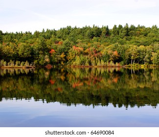 Fall foliage reflected in the still water of a lake in the lakes region of Maine.